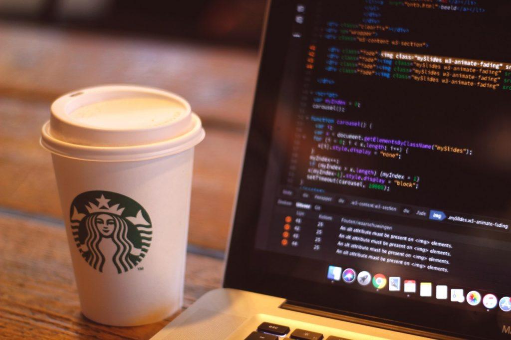 htmlが映ったノートPCの画面とスタバのコーヒー
